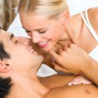 Portrait of young attractive happy amorous couple in bedroom — Stock Photo