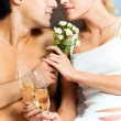 Young happy amorous couple with champagne at bedroom — ストック写真