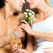 Young happy amorous couple with champagne at bedroom — Stock Photo