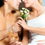 Genç mutlu sevdalı çift yatak odası, şampanya ile — Stok fotoğraf