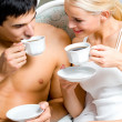 Young happy smiling couple drinking coffee at bedroom — ストック写真