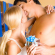 Young happy couple with gift-box embracing and kissing at home — Stock Photo