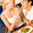 Funny scene of young happy couple playfully eating at kitchen — Stock Photo