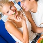 年轻快乐的夫妻,调皮地在厨房吃的滑稽场面 — 图库照片