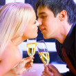 Young happy couple with champagne kissing at restaurant — Stockfoto