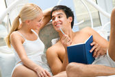 Young attractive happy smiling couple with notebook in bedroom — Stock Photo