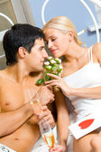 Young happy couple celebrating with champagne at bedroom — Stock Photo