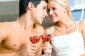 Young happy amorous couple celebrating with red wine at bedroom — Stock Photo
