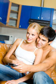 Young happy couple watching TV togeher at home — Stock Photo