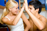 Young happy smiling amorous couple gesturing a victory, at home — Stock Photo