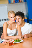 Young happy amorous couple at domestic kitchen — Stock Photo