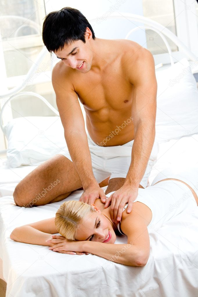 Young happy couple making massage in bedroom — Stock Photo #6763846