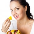 Young smiling woman with bowl of fruits, isolated on white background — Stock Photo
