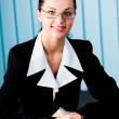 Happy smiling businesswoman with pen and glasses at office — Stock Photo #6770396