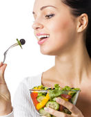 Young happy smiling woman eating vegetable salad, isolated — ストック写真