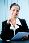 Happy smiling businesswoman with pen at office — Stock Photo