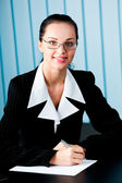 Happy smiling businesswoman with pen and glasses at office — Stock Photo