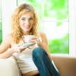 Young smiling woman drinking coffee, at home — Stock Photo