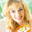 Young smiling woman eating muslin at home — Stock Photo #6830658