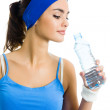 Woman in sportswear drinking water, isolated — Stock Photo