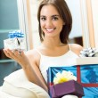 Happy smiling woman with gifts at home — Stock Photo