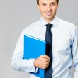 Portrait of business man with folder, over gray — Stock Photo #7036797