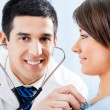 Doctor with stethoscope and patient at office — Stock Photo