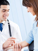 Happy doctor giving an injection to female patient — Stock Photo
