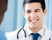 Smiling doctor and female patient at office — Stock Photo