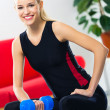 Woman exercising with dumbbell on fit ball, at home — Stock Photo