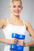Woman exercising with dumbbells, at home — Stock Photo