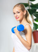 Woman exercising with dumbbell, at home — Stock Photo