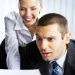 Stock Photo: Two businesspeople working with document at office