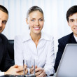 Three happy businesspeople at office - Stock Photo