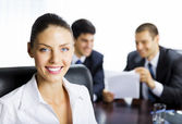 Businesswoman and colleagues, at office — Stock Photo
