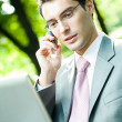 Business man working with laptop and cellphone, outdoors — Foto Stock