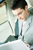 Businessman working with laptop in the car — Stock Photo