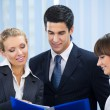 Three young happy businesspeople at office — Stock Photo