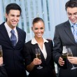 Happy smiling young businesspeople celebrating with champagne at — Stock Photo