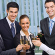 Happy smiling young businesspeople celebrating with champagne at — Stock Photo #7511213
