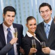 Happy smiling young businesspeople celebrating with champagne at — Stock Photo #7511230