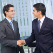 Two businesspeople cheering by handshake at office — Stock Photo #7511336