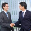 Two businesspeople cheering by handshake at office — Stock Photo