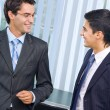 Two happy successful businessmen talking at office - Stock Photo