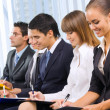 Photo of businesspeople or students at conference - Stock Photo