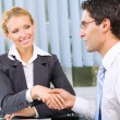 Two businesspeople cheering by handshake or flirting at office — Stock Photo