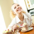 Young happy smiling beautiful young woman eating torte at home — Stock Photo