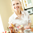 Young happy smiling beautiful young woman eating torte at home - Stock Photo