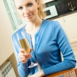 Portrait of young woman with glass of champagne, at home — Stock Photo