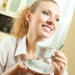 Young smiling woman drinking coffee, at home — Stock Photo #7543377